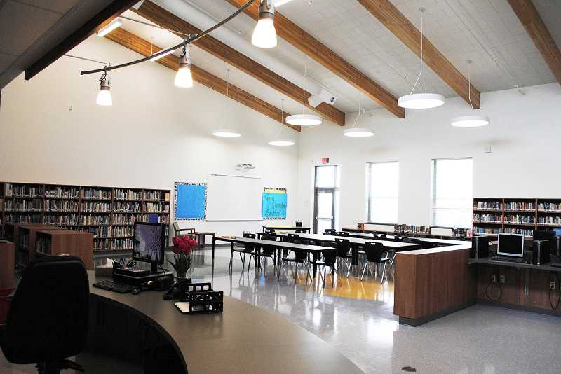 by: NEWS-TIMES PHOTO: STEPHANIE HAUGEN - During spring break, helpers moved books into the new library, which features natural lighting and a computer lab.