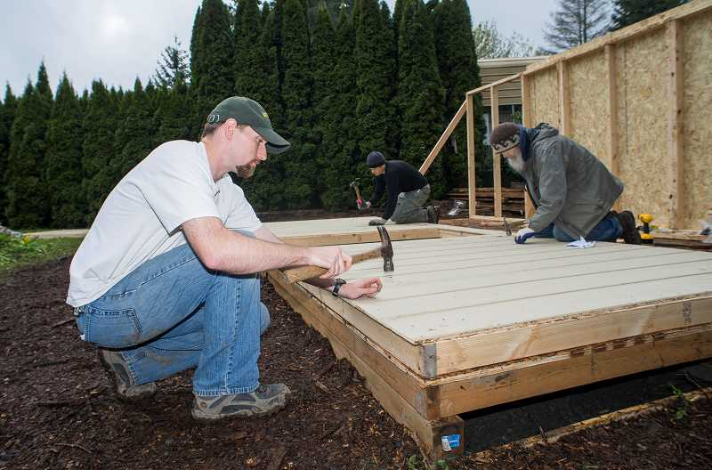 by: NEWS-TIMES PHOTO: CHASE ALLGOOD - Josh Jacobson, Jeremy Wilson, and David Rudkin (left to right) nail in the siding on a shed they are helping to build for Forest Grove resident Rebecca Cohoon.