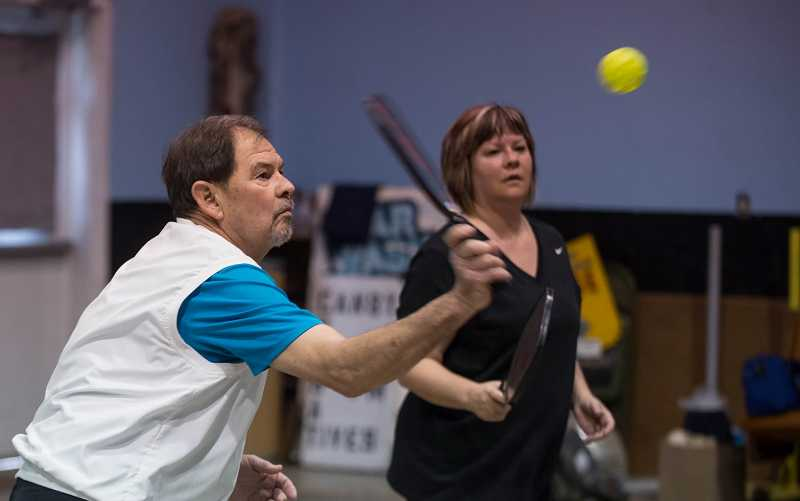 by: RAY HUGHEY - Dale Rohrscheib, of Canby, left, concentrates on a return as he and daughter Angela Cordry, of HIllsboro, defend their side of the court in a game of pickleball.