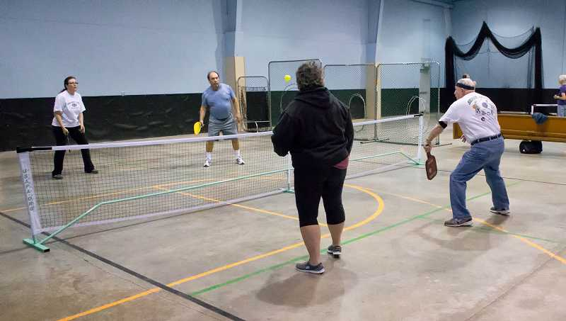 by: RAY HUGHEY - From left, Theresa Felix, Dan Collins, Peg Rohrscheib and Clay Metzger battle it out on the pickleball court.