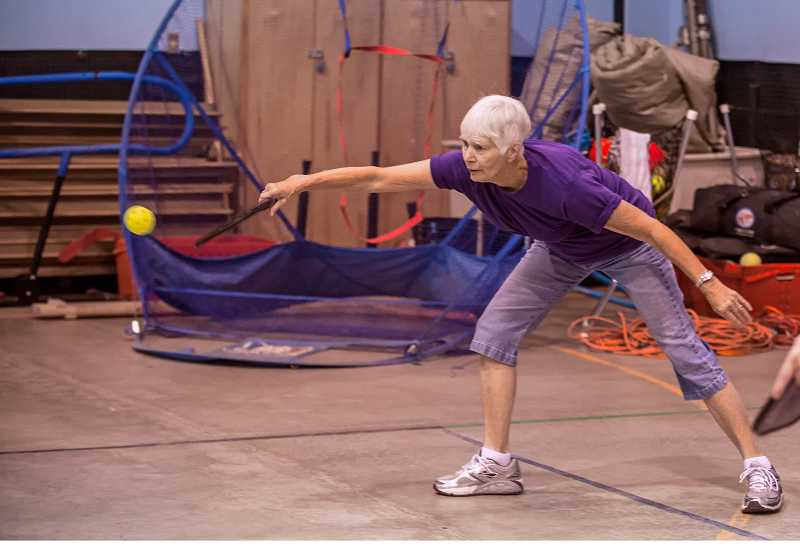 by: RAY HUGHEY - Pickleball fan Jean Metzger stretches to make a return.