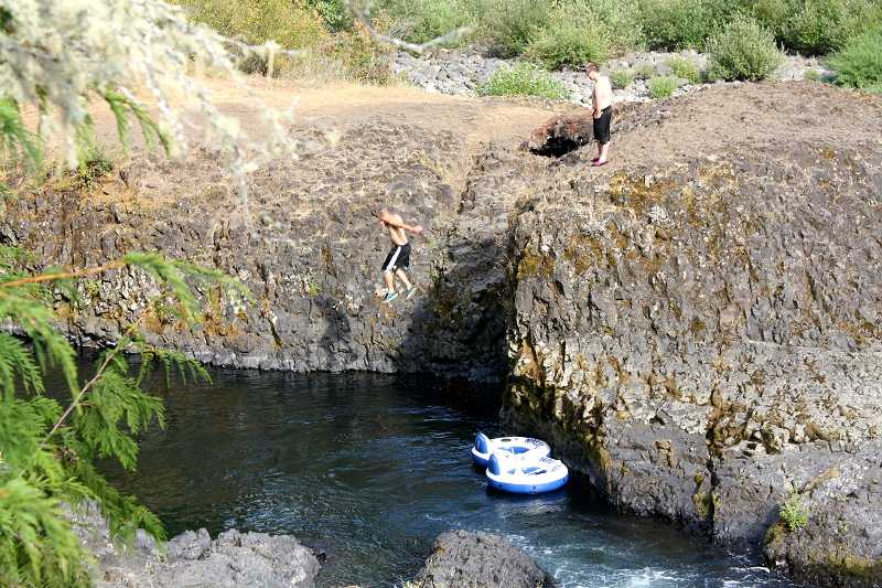 by: PEGGY SAVAGE - Swimmers jump from Big Bear Rock on the Molalla River Corridor, a popular spot for tourists on hot summer days