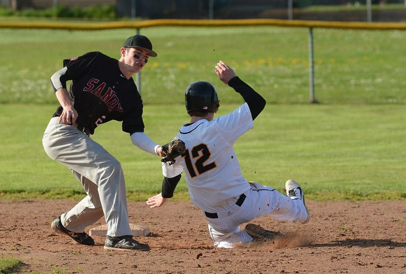 by: JOHN WILLIAM HOWARD - Bryce Mulcahy slides into second base in the fifth inning. St. Helens scored both their runs in the fourth en route to a 2-0 defeat of Sandy.
