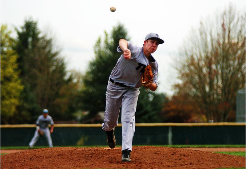 by: DAN BROOD - HERE IT COMES -- Tualatin junior pitcher Jacob Bennett fires a pitch to the plate during the Wolves' 8-0 win at Newberg on Tuesday.