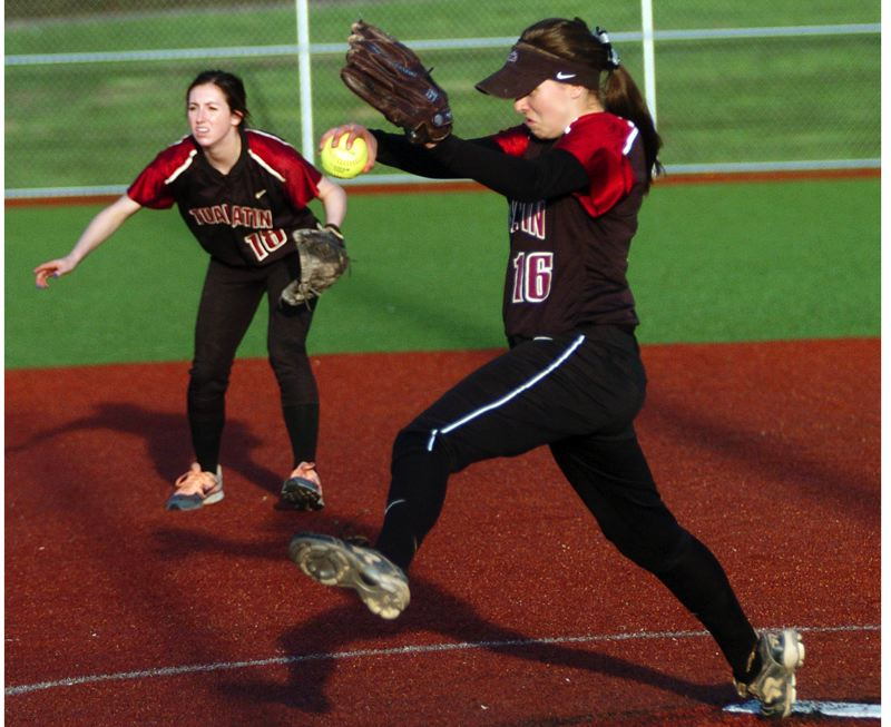 by: DAN BROOD - DEALING HEAT -- Tualatin High School junior Emily Sorem, in front of shortstop Joslyn Gastiaburu, gets ready to fire a pitch to the plate during Monday's game with West Linn. Sorem had 17 strikeouts for the Timberwolves in their 6-0 victory.