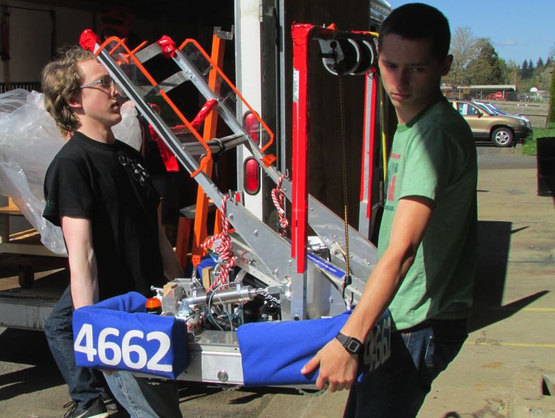 by: MARK MILLER - Tribal Tech team captains Robert Ohling, left, and Travis Gardner, right, unload Scappoose High School's robot from a trailer at the school Wednesday, April 9.