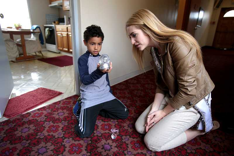 by: TIMES PHOTO: JONATHAN HOUSE - Miss Oregon Emma Pelett hangs out with Omar, the son of a resident, during a tour of the new LifeChange Center for Women and Their Children in Beaverton on Friday.