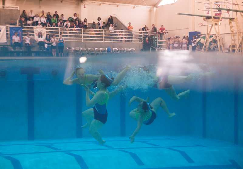 by: TIMES PHOTO: JONATHAN HOUSE - Members of the Tualatin Hills Synchro Team get ready for their next move in the 11-12 Age Group category during the Oregon Association of Synchronized Swimmings Classic Invitational competition Saturday in Beaverton.