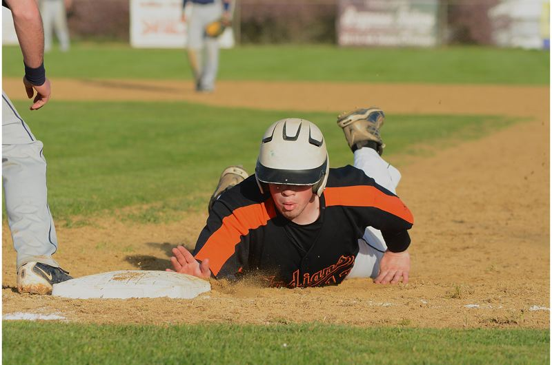 by: JOHN WILLIAM HOWARD - Senior Will Sprute dives back to first base to avoid a pick off in the fifth inning.