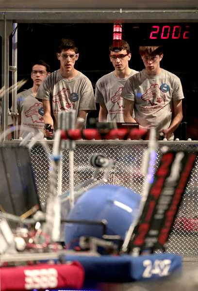 by: TIMES PHOTO: JONATHAN HOUSE - Jorge Reyes, Brian Hillenbrand and Jason Stallkamp of the Tualatin Robotics Team operate their robot during the Pacific Northwest FIRST Robotics District Championship.