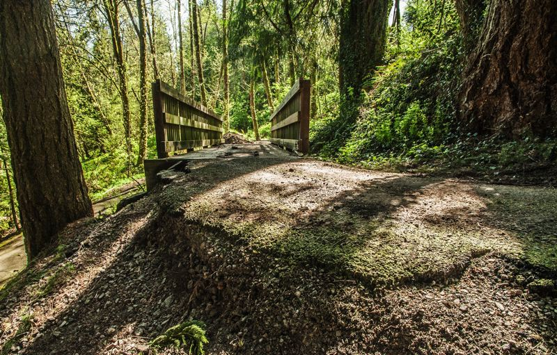 by: SPOKESMAN PHOTO: JOSH KULLA - Erosion has damaged the Boeckman Creek Crossing trail in Wilsonville to the point where it is undercutting the paved trail. The trail will be closed through May for repairs.