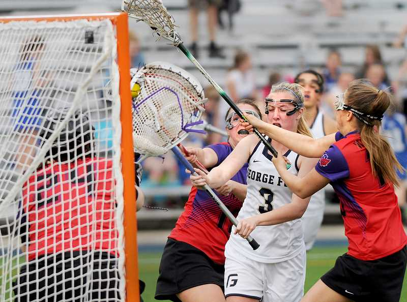 by: SETH GORDON - Traffic jam - Freshmen Christine Doherty attempts a shot during George Fox's 15-5 win over Linfield at home April 8. The Bruins finished 6-6 in their debut season as a program.