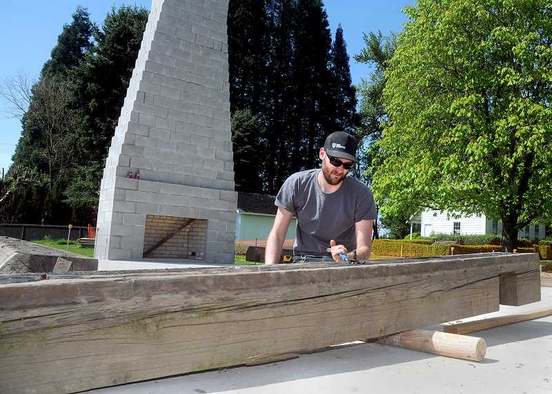 by: GARY ALLEN - Getting started - Adam Leckie, a carpenter for Arciform of Portland, prepares large beams Friday to be moved into place this week at the new home of the Pioneer Mother's Historical Cabin adjacent to the Robert Newell House Museum.