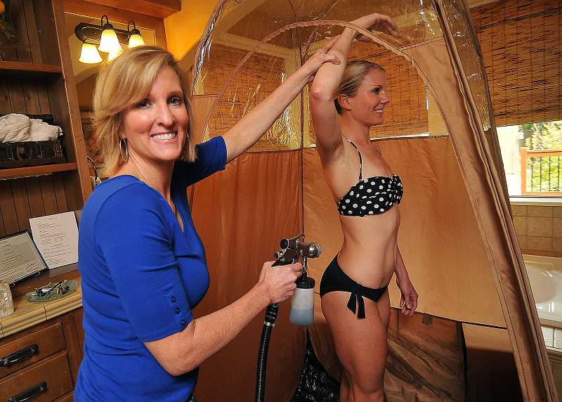 by: TIDINGS PHOTO: VERN UYETAKE - Stacey Mickey, left, started her organic airbrush tanning business two years ago in an attempt to combat skin cancer risks. Charity Hess, right, is one of her most loyal clients.