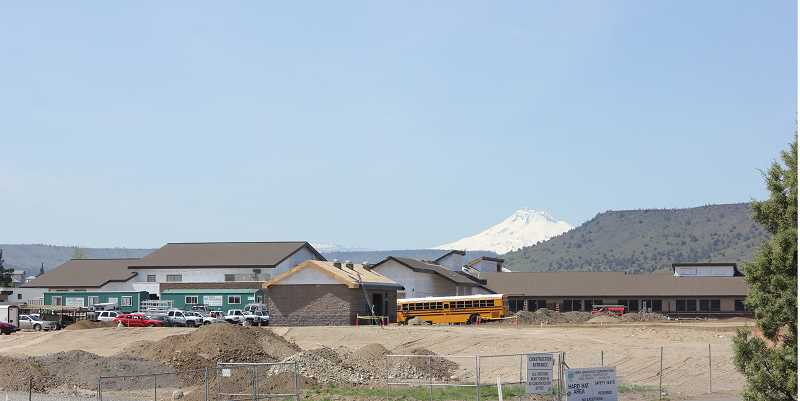 by: SUSAN MATHENY/MADRAS PIONEER - Mount Jefferson looms behind the new school under construction.