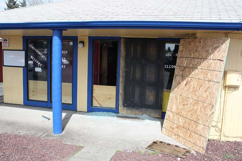 by: NEWS-TIMES PHOTO: DOUG BURKHARDT - Boarded-up windows and shattered glass outside K & S Wholesale Inc. on Pacific Avenue are remnants of an armed robbery that occurred at the Forest Grove busines April 9.