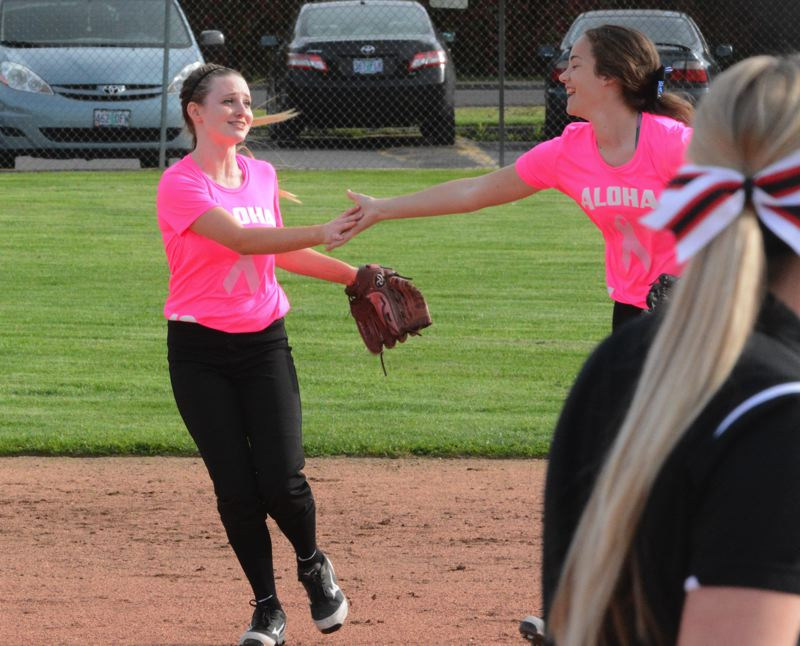 by: TIMES PHOTO: MATT SINGLEDECKER - Aloha rightfielder Cidney Marshall and first baseman Lexi Wahlstrom celebrate Marshalls key defensive stop in the second inning against McMinnville.