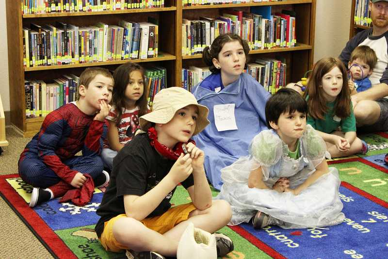 by: CONTRIBUTED PHOTO: ERIC SQUIRES - Enraptured children listen to storybook tales read to them during the grand opening celebration for the new Aloha Community Library at 17455 S.W. Farmington Road. Children dressed up as their favorite characters for an earlier parade from the old facility to the larger space to the east.