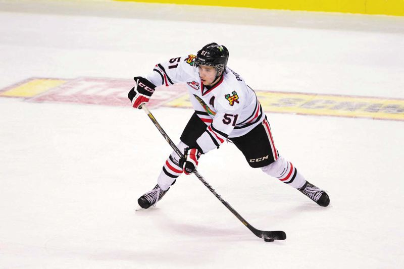 by: TRIBUNE PHOTO: JAIME VALDEZ - Veteran defenseman Derrick Pouliot, a mainstay on the Portland Winterhawks potent power-play first unit, looks to pass in a first-round playoff game against Vancouver.