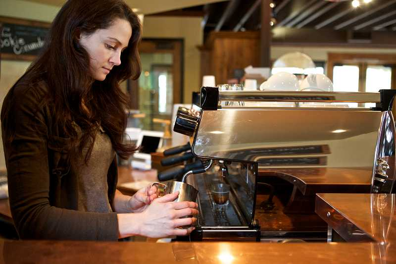 by: TIMES PHOTO: JAIME VALDEZ - Barista Amanda Smithberger makes a latte at Well & Good Coffee in Tigard. The café opened in March in the former site of Beveland Street Bistro off Southwest 72nd Avenue.