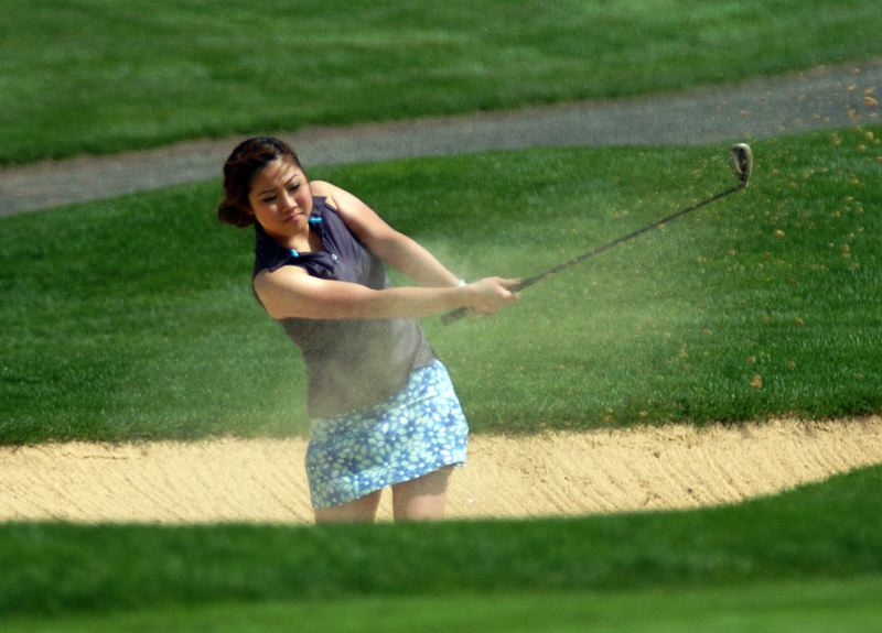 by: DAN BROOD - FROM THE BEACH -- Tigard senior Sooji Kim chip out of the bunker during play Monday at the Pacific Conference tournament held at Tualatin Country Club.