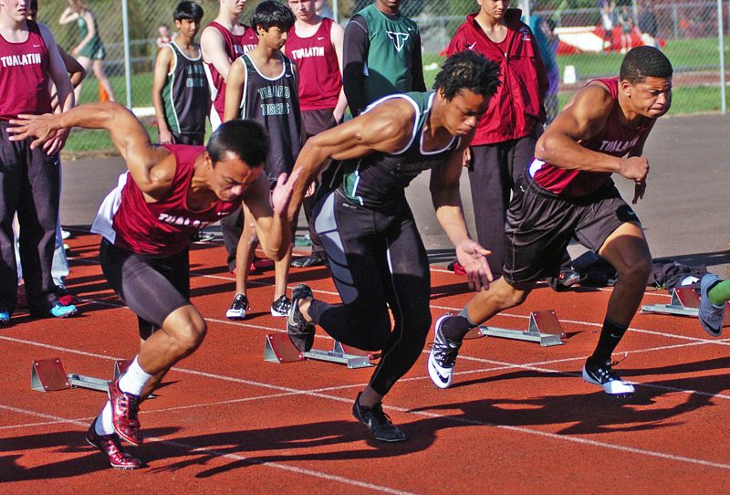 by: DAN BROOD - THERE THEY GO -- Tigard junior Landon Floyd (center) got off to a fast start on his way to winning the 100-meter dash.