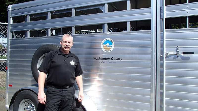 by: SUBMITTED PHOTO - Randy Covey, animal services field supervisor with the Animal Multi-Agency Coordination Group, shows off one of four large animal transport trailers recently purchased to use in emergency response situations across the Portland area.