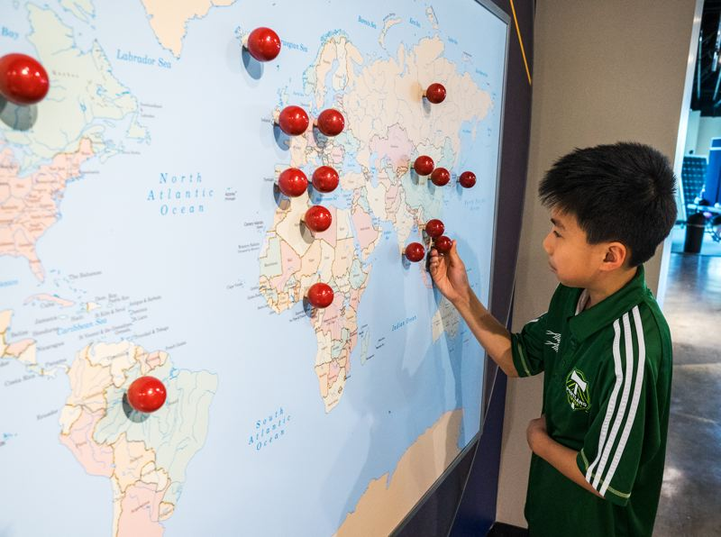 by: HILLSBORO TRIBUNE PHOTO: CHASE ALLGOOD - Hillsboro resident Nien Nguyen, 10, works with an interactive map display during  Free Family Day April 12 at the Washington County Museum.