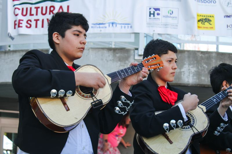 by: HILLSBORO TRIBUNE PHOTO: JOHN SCHRAG - Guitarists with the Una Voz Mariachi Band rock the crowd with traditional music and song. The band is comprised entirely of students from the Hillsboro School District.