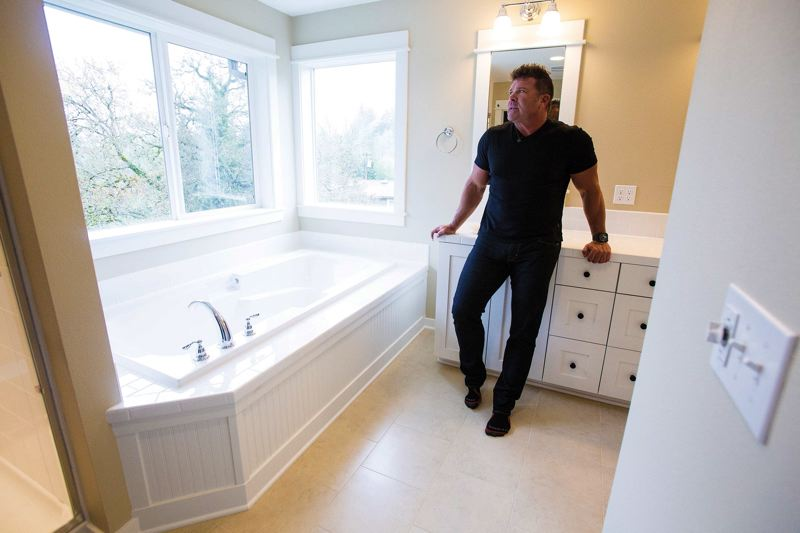 by: TRIBUNE PHOTO BY JONATHAN HOUSE - Standing in the bathroom of one of his new house models in Multnomah Village, Randy Sebastian of Renaissance Homes talks about its amenities. Sebastian supports mandatory notification of neighborhood demolition plans.