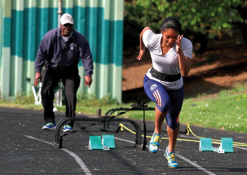 by: TRIBUNE PHOTO: JONATHAN HOUSE - Benson High track and field star Jasmin McKenzie gets guidance from her grandfather, Leon McKenzie, who happens to be her coach.