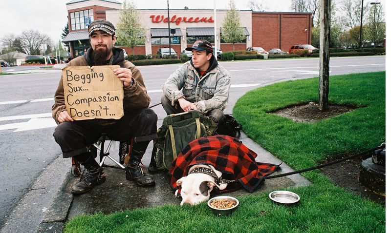 by: PHOTO BY: JOHN DENNY - Their sign says it all, as Trinidad Rodriguez (left), his dog, and street brother James Ormsby greet motorists as they exit Milwaukie Marketplace.