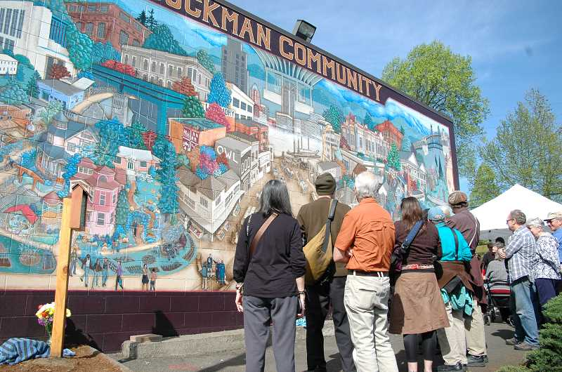 by: ISABEL GAUTSCHI - A crowd gathered for the Joe Cotter kiosk dedication in front of the Buckman Community Mural in Portland on Friday, April 18.
