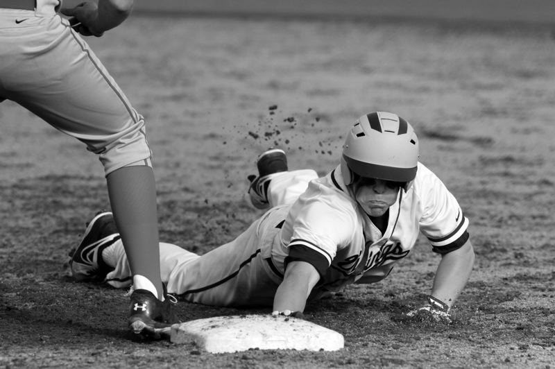 by: NEWS-TIMES PHOTO: AMANDA MILES - Forest Grove junior Andrew Thorud dives back into first base during last Friday's game against McMinnville.
