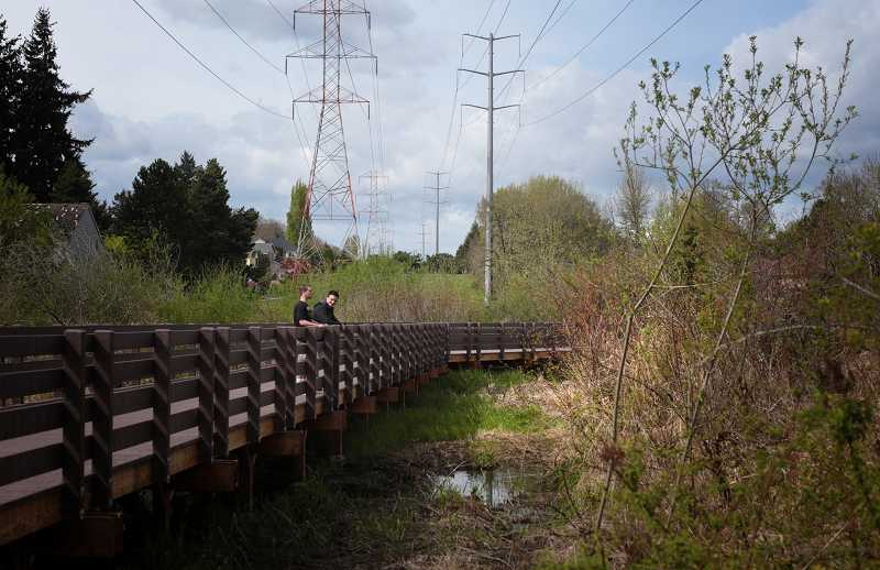by: TIMES PHOTO: JONATHAN HOUSE - Tucker Spooner and Avik Bordack wait for a friend while checking out the view from the new bridge across Bronson Creek in Bethany.