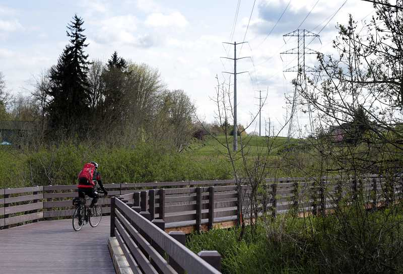 by: TIMES PHOTO: JONATHAN HOUSE - A cyclist rides on the new Bronson Creek Bridge in Bethany. The crossing helps complete one of the final segments in the 5.5-mile Waterhouse Trail.