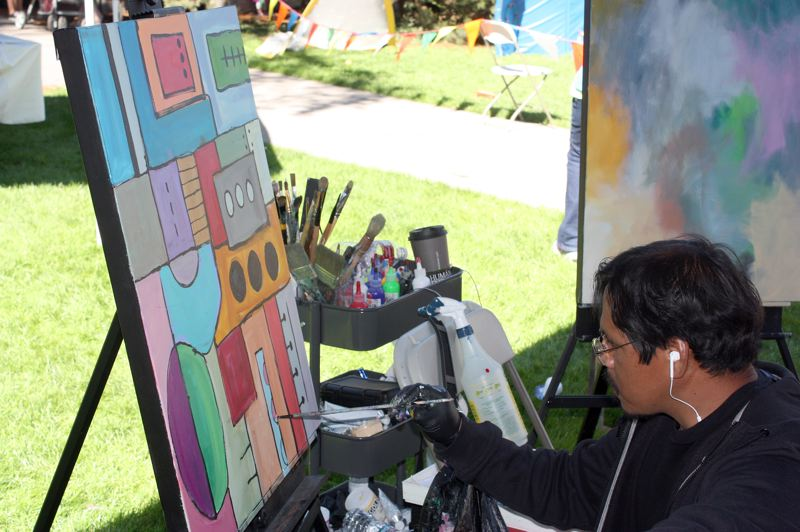 by: HILLSBORO TRIBUNE PHOTO: DOUG BURKHARDT - Forest Grove painter Plata Garza creates an abstract painting under the artists' tent during Sunday's Latino Cultural Festival in downtown Hillsboro.