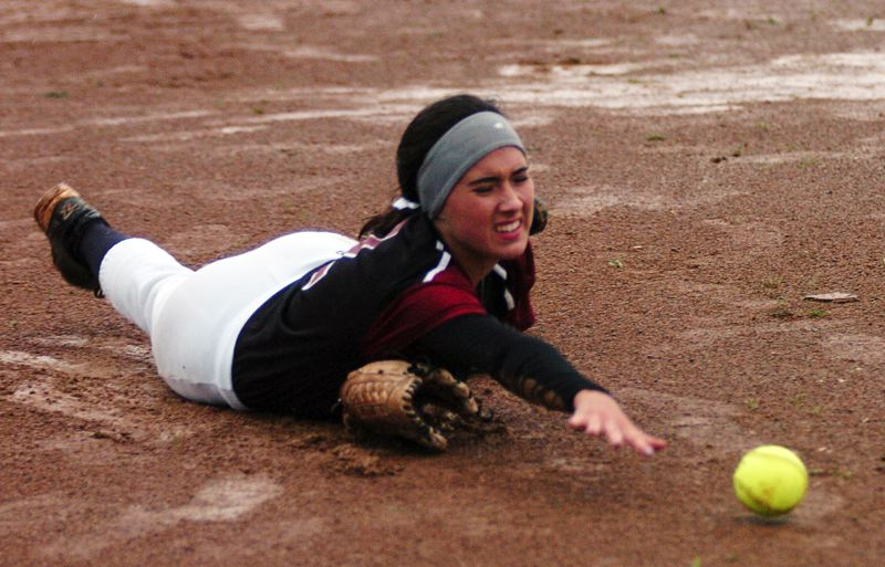 by: DAN BROOD - GETTING MUDDY -- Tualatin senior second baseman Beth Fanger dives to try and grab the ball during Monday's game.