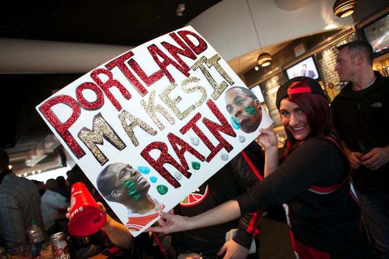 Fan Lizzie Cox of Milwaukie holds up a sign she made for Game 3.