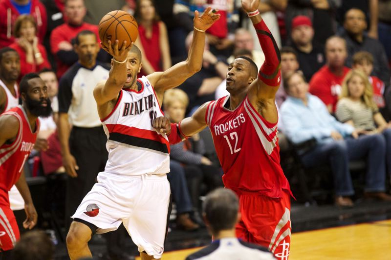 Nicolas Batum of Portland goes for an overtime layup inside the defense of Houston and Rockets center Dwight Howard.
