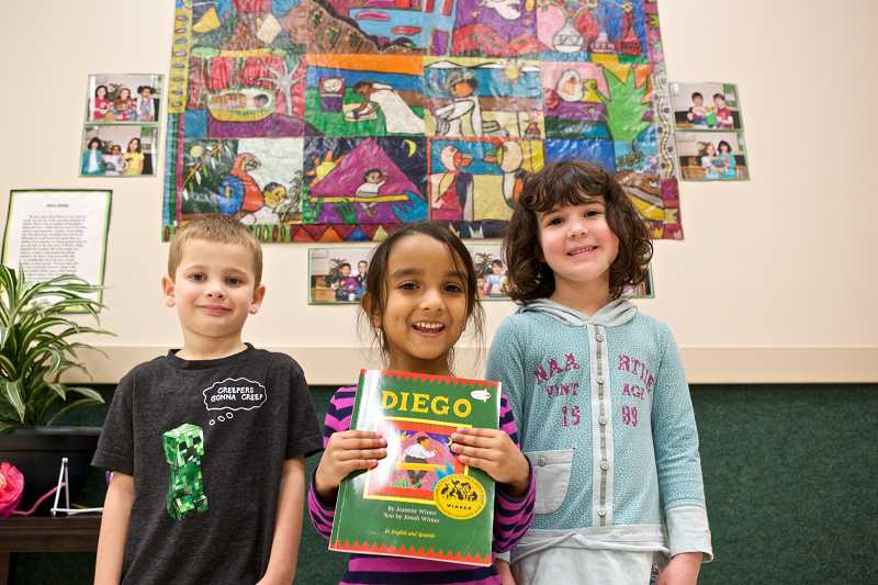 by: JAIME VALDEZ - Five-year-olds Logan Bowersock, left, Anika Krishnamoorthy and Molly Clancy stand in front of an art piece that their preschool class made inspired by artist Diego Rivera at Touchstone School in Tigard. The school will launch a pilot program this fall to bring Spanish immersion classes to the 4-year-old students.