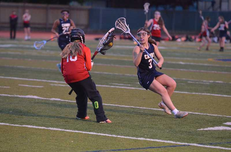 by: JEFF GOODMAN / PAMPLIN MEDIA GROUP - Bailee Mallon (right) pressures Clackamas goalkeeper Hope Murray during the Canby girls lacrosse team's home game April 25. The Cougars are trying to remain positive amid a trying season under first-year coach Kristen Brown.