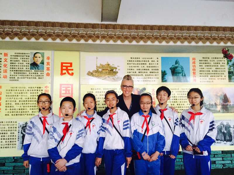 by: COURTESY OF HEATHER CORDIE - Sherwood Superintendent Heather Cordie poses with students from an elementary school in Fugu County in China. The students provided Cordie with an overview and history of their school during a recent trip with other educators from the United States.