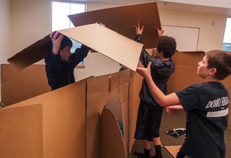 by: SPOKESMAN PHOTO: JOSH KULLA - Community of Hope Church youth group members construct cardboard shelters as part of the 30 Hour Famine, a fundraising effort to benefit the poor, even those close to home.