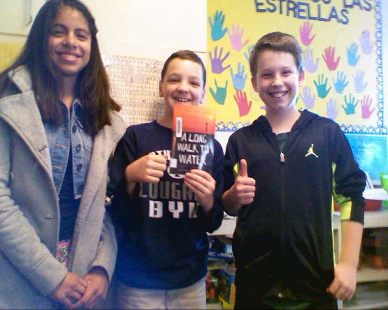 by: MARGOT HACKMAN - Lincoln Elementary School fifth-graders (from left) Marina Thomer, Kaden Christiansen and Josiah Peterson hold up the book 'A Long Walk to Water,' which was read in class and inspired them to raise money for the malnourished people living in South Sudan. The trio's class is hosting a yard sale May 10 to raise funds for Water for South Sudan from 9 a.m. to 3 p.m. in front of the school, located at 1041 N. Boones Ferry Road in Woodburn.