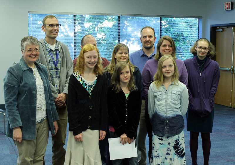 by: NEWS-TIMES PHOTO: JOHN SCHRAG - Rotarian Pat Truax (left) posed with Claire Hansen,  Shayna Olsen and Victoria Rockey and their family members after the three students read their winning essays to the Daybreak Rotary Club on Tuesday morning.