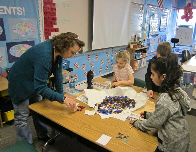 by: SHERWOOD GAZETTE: BARBARA SHERMAN - Archer Glen Elementary artist-in-residence Lisa Wilcke (left) spreads glue on wind-catchers made by second-graders Avery Morse (center) and Valeria Bravo, which was the second of three projects the kids did.