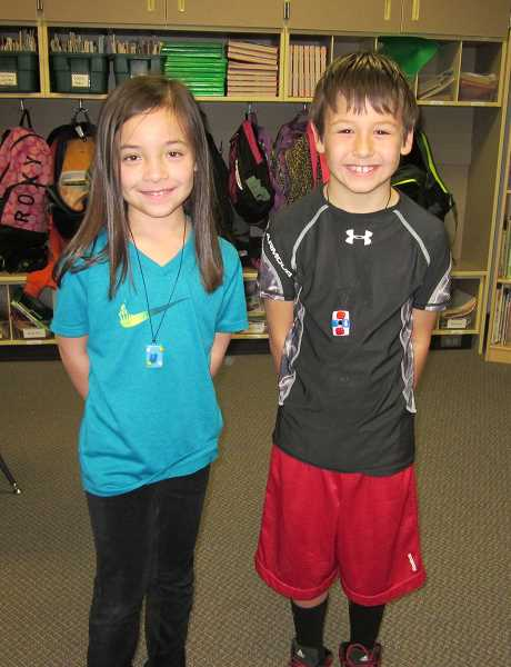 by: SHERWOOD GAZETTE: BARBARA SHERMAN - Proudly wearing pendants they created after artist-in-residence Lisa Wilcke took then home and fired them in her kiln are Archer Glen Elementary second-graders Kayla Lee and Nigel Fahland.