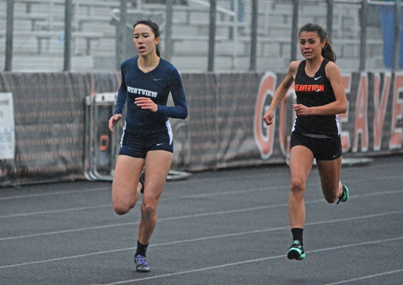 by: TIMES PHOTO: MATT SINGLEDECKER - Westview's Laura Gastineau nudged past Beavertons Cassandra Harrigan in the 400-meter dash on on April 23.