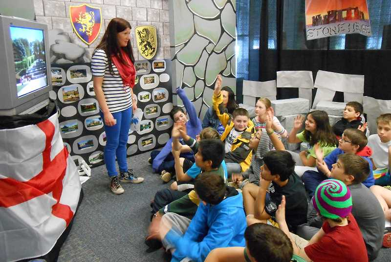 by: REVIEW PHOTO: JILLIAN DALEY - Lake Grove students listen to volunteer Lisa McAuley after watching an educational video during the Culture Travels event last week.